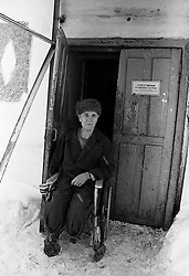 An old man seats on his invalid chair in front of enter of barrack where he lives in house for  released an old prisoners in village Blagoveshenka, Kemerovo region, Eastern Siberia, Russia, 08 December1999. Blagoveshensky house for an old former prisoners a special institution which is a part of a penitentiary system where live former prisoners which have age more then 55 years after released and haven't house or an apartment and relatives.