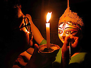 Caption : Due to vehement loadsheding, under a lamp an Indian artisan has been compelled to draw the eyes of the idol of Durga, the Hindu goddess of power, at Kumartuli of Dhubri, about 293 kilometres southwest of Guwahati, capital of Northeastern Indian state of Assam, Tuesday, September 27, 2005. .The annual five-day prayer of  Durga Puja festival starts on October 08 across the country and abroad, which is one of the most popular Hindu festivals in India. In Hindu mythology, Durga symbolizes power and the triumph of good over evil. (Shib Shankar Chatterjee)