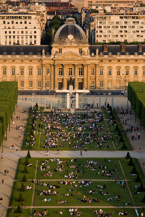 Groups of people picnicking on the grass of Parc du Champ de Mars in in the shadow of the Eiffel Tower at sunset, Paris, France<br />