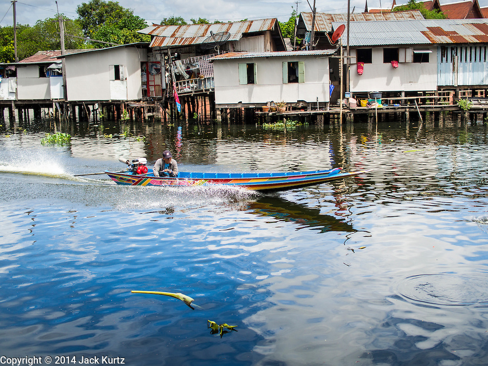 "11 JULY 2014 - BANGKOK, THAILAND:   A man takes his small ""long tail boat"" up a khlong (canal) behind Wat Mahabut in Bangkok.   PHOTO BY JACK KURTZ"