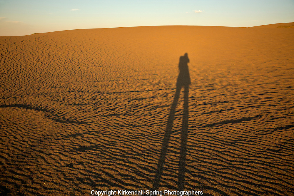 ID00646-00...IDAHO - Hiker on the sand dunes at sunset in Bruneau Dunes State Park.