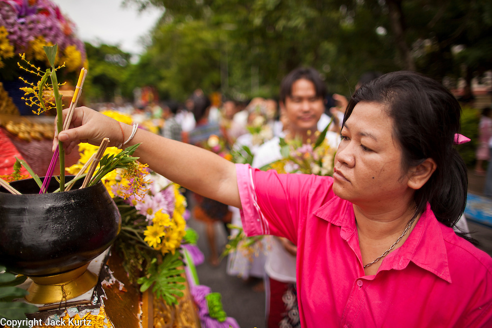 """15 JULY 2011 - PHRA PHUTTHABAT, SARABURI, THAILAND:   A woman presents flowers to a float carrying a robed statue of the Buddha during the Tak Bat Dok Mai at Wat Phra Phutthabat in Saraburi province of Thailand, Friday, July 15. Wat Phra Phutthabat in Phra Phutthabat, Saraburi, Thailand, is famous for the way it marks the beginning of Vassa, the three-month annual retreat observed by Theravada monks and nuns. The temple is highly revered in Thailand because it houses a footstep of the Buddha. On the first day of Vassa (or Buddhist Lent) people come to the temple to """"make merit"""" and present the monks there with dancing lady ginger flowers, which only bloom in the weeks leading up Vassa. They also present monks with candles and wash their feet. During Vassa, monks and nuns remain inside monasteries and temple grounds, devoting their time to intensive meditation and study. Laypeople support the monastic sangha by bringing food, candles and other offerings to temples. Laypeople also often observe Vassa by giving up something, such as smoking or eating meat. For this reason, westerners sometimes call Vassa the """"Buddhist Lent."""" The tradition of Vassa began during the life of the Buddha. Most of the time, the first Buddhist monks who followed the Buddha did not stay in one place, but walked from village to village to teach. They begged for their food and often slept outdoors, sheltered only by trees. But during India's summer rainy season living as homeless ascetics became difficult. So, groups of monks would find a place to stay together until the rain stopped, forming a temporary community. Wealthy laypeople sometimes sheltered monks on their estates. Eventually a few of these patrons built permanent houses for monks, which amounted to an early form of monastery.   PHOTO BY JACK KURTZ"""