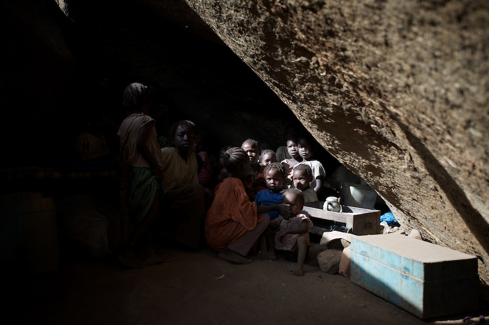 April 28, 2012 - Buram, Nuba Mountains, South Kordofan, Sudan: A Nuba family takes cover, from possible bombardments by Sudan's Army Forces airplane, in some caves near Buram village...Since the 6th of June 2011, the Sudan's Army Forces (SAF) initiated, under direct orders from President Bashir, an attack campaign against civil areas throughout the South Kordofan's province. Hundreds have been killed and many more injured...Local residents, of Nuba origin, have since lived in fear and the majority moved from their homes to caves in the nearby mountains. Others chose to find refuge in South Sudan, driven by the lack of food cause by the agriculture production halt due to the constant bombardments of rural areas. (Paulo Nunes dos Santos/Polaris)