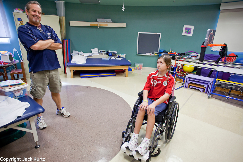 30 DECEMBER 2009 -- PHOENIX, AZ: Mackenzie Saunders (CQ) talks her dad, Gary Saunders (CQ) after physical therapy at St. Joseph's Hospital in Phoenix Wednesday. Mackenzie was knocked down by another player during a soccer game. She finished the game but later in the day her legs started hurting and her parents took her to a hospital. Three hospitals later, she was in St. Joseph's with a diagnosis of a swollen spine and she couldn't walk. Now she's in physical therapy. She is expected to make a full recovery but her doctors have said she won't be able to play soccer for at least another 16 months.       Photo by Jack Kurtz