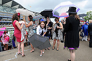 © licensed to London News Pictures. ASCOT, UK.  16/06/11. Ladies rush to put up the umbrellas. Ladies Day at Royal Ascot 16 June 2011. Royal Ascot has established itself as a national institution and the centrepiece of the British social calendar as well as being a stage for the best racehorses in the world. Mandatory Credit Stephen Simpson/LNP