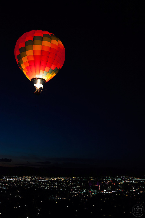 """Dawn Patrol 11"" - Photograph of a glowing hot air balloon flying for the Dawn Patrol at the 2012 Great Reno Balloon Race. Photographed from a hot air balloon."