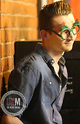 Manchester UK  24.12.2016: Images from Manchesters Gay Village during the Mad Friday celebrations this on the 23 and 24th of December,<br /> <br /> <br /> A Teen stands smiling to himself wearing funny glasses