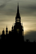 London-Nov 2006: Gothic spires of the Houses of Parliament sihoetted against a moody green sunset with plume of smoke on 12 Nov in Westminster
