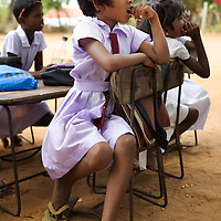An outdoor class in the grounds of the Thikilivattai Government Tamil Mixed School in Batticaloa District. <br /> <br /> Thikilivattai Government Tamil Mixed School reopened in May 2008 after local conflict between the LTTE and SLA  troops eased. There are now 351 students in grades 1-9 with a teaching staff of 18. The school has no water supply. Though many of the pupils' parents are not well educated themselves (most are employed in casual paddy cultivation, fishing and seasonal day-wage labour), there is a parents' mobilisation committee that encourages pupil attendance and is involved in helping keep the school clean. The school has an active sports department. Many of the students suffer with the trauma and stress associated with those living in conflict situations. The staff must deal with these issues as well as the personal difficulties that they themselves suffer living in a conflict environment. UNICEF have provided three temporary learning spaces to make up for the lack of space in the original school building. A further two classes must be accommodated beneath trees. UNICEF have also supplied the school furniture.<br /> <br /> Photo: Tom Pietrasik<br /> Batticaloa District, Sri Lanka<br /> September 30th 2009