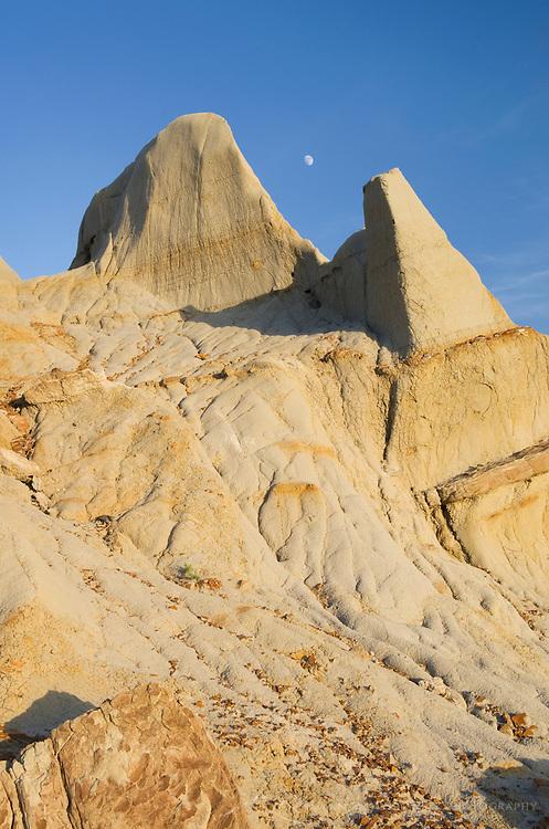 Moon over badlands sandstone formations Theodore Rossevelt National Park, North Dakota