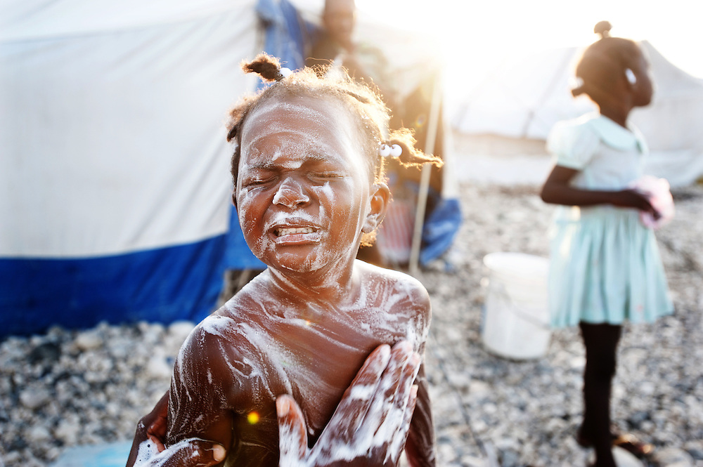 A child gets washed in a tent settlement in Tabare Issa, Port au Prince.