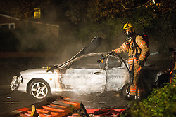 © Licensed to London News Pictures . 05/11/2015 . Oldham , UK . A fireman damps down a burned out car on West End Street . Manchester Fire reports receiving more than 300 calls in less than 7 hours, from 4.30pm, including to buildings, cars and wheelie bins set alight by arsonists . At some calls fire crews were subject to vandalism , including a hose being sliced whilst it was being used to fight a fire in Leigh and bricks being thrown at crews attending a job in Miles Platting . Fire crews deal with arson attacks across Greater Manchester during Bonfire Night . Photo credit : Joel Goodman/LNP