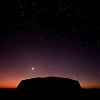Australia, Northern Territory, Uluru - Kata Tjuta National Park, Dawn silhouettes Ayers Rock on summer morning in Outback