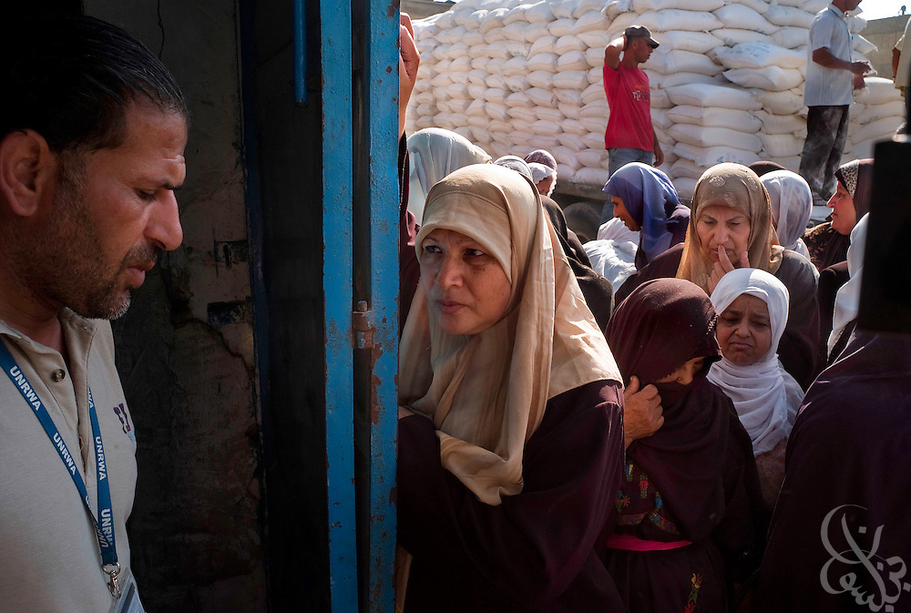 "Palestinian women cue for United Nations food distributions August 05, 2007 in Gaza City, Gaza. The United Nations recently warned that Gaza faces an economic meltdown with ""disasterous consequences"" unless the crossings into the territory are opened again. The crossings have remained closed by Israel since the violent takeover of Gaza by Hamas in June."