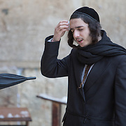 An ultra-orthodox man wipes snow on his face as snow and rain fall at The Western Wall on January 7, 2015 in Jerusalem, Israel. (Photo by Elan Kawesch)