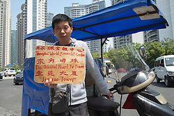 Motorcycle taxi driver offering tour guide services in Shanghai China