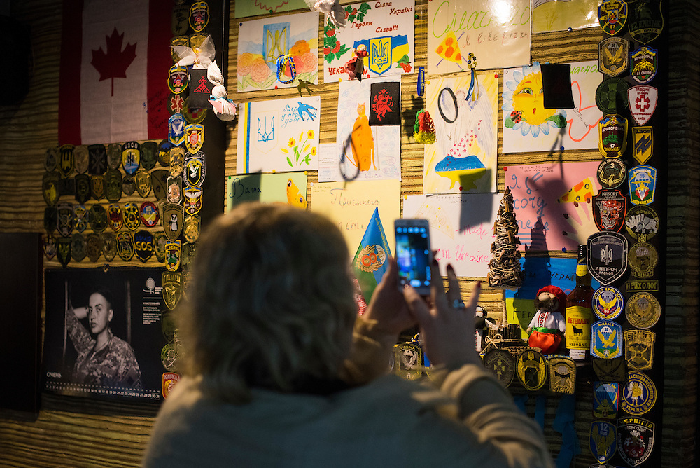 Irina Kondratyk, a customer, photographs a wall and shelf of ephemera at Veterano Pizza on January 23, 2016 in Kiev, Ukraine. (Pete Kiehart for The New York Times)