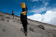 A porter on Mount Kilimanjaro carries a bucket of water towards the clouds and the base camp at roughly 15,000 ft. A stream below the camp where clients embark to the summit of the mountain is the only source of water and porters are forced to carry 5 gallon buckets, or roughly 40 pounds, up the steep grade.
