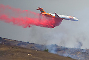 July 13, 2015 - Yorba Linda, CA, USA - <br /> <br /> water planes take to the sky to help put out fires<br /> <br /> An air tanker douses burning brush with fire retardant off the 241 toll road Monday near Irvine and Orange. More than 150 acres burned in unincorporated Orange County, California <br /> ©Exclusivepix Media