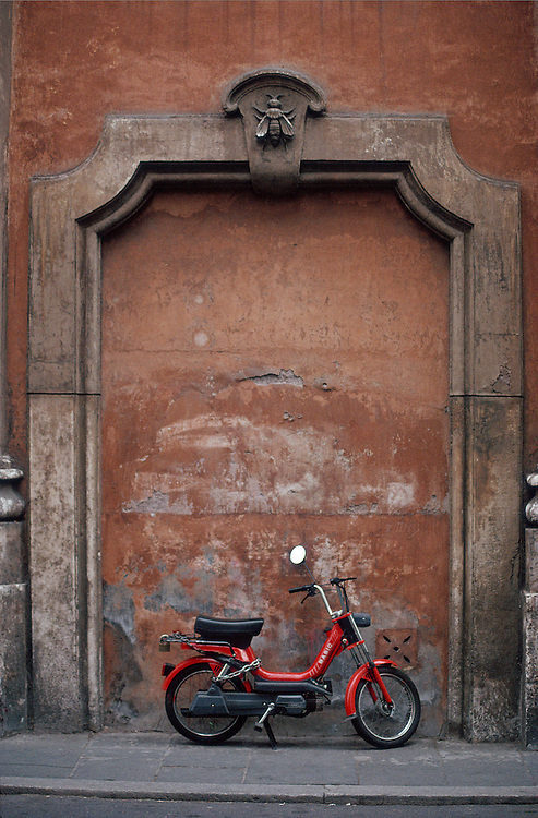 A red motorbike is parked on a sidewalk, against a stucco wall framed by an arch, adorned with a plaster bee