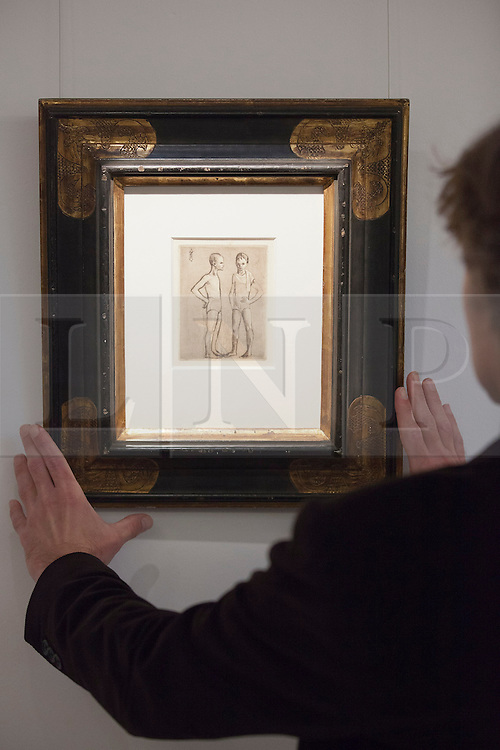 © Licensed to London News Pictures. 13/09/2013. London, UK. A Sotheby's employee adjusts 'Les Deux Saltimbanques' (est. GB£20,000-30,000) an etching by Pablo Picasso at the press view for Sotheby's 'Prints and Multiples Sale' on New Bond Street in London today (13/09/2013). The auction, set to take place on the 17th of September, includes works by Munch, Rembrandt, Basquiat, Warhol and Picasso. Photo credit: Matt Cetti-Roberts/LNP