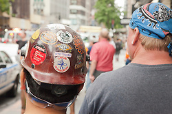 back of men's heads in New York City with union worker stickers on a hard hat and a bandana