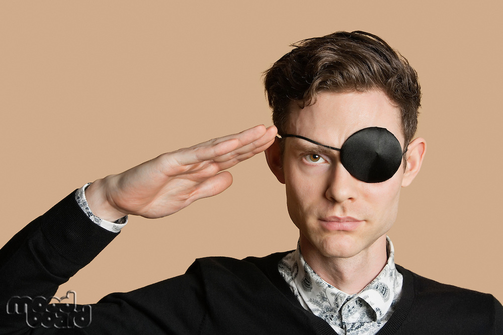Portrait of a man wearing eye patch saluting over colored background