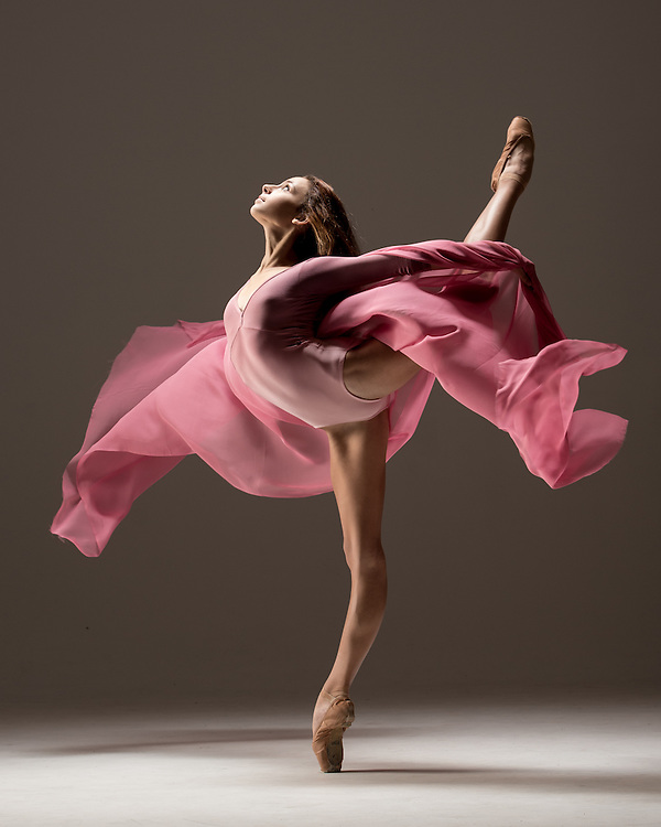 Classical ballet ballerina, Juliette Bosco, in an attitude with a pink dip dye leotard from Yumiko, with a flowy pink fabric. Taken in the photo studio on a grey background. Photograph taken in New York City by photographer Rachel Neville.