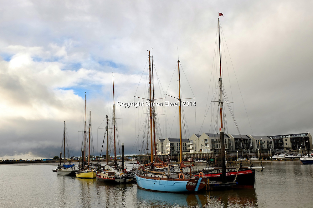 Colourful Traditional fishing boats (smacks) moored up in the creek at Brightlingsea Harbour in Essex