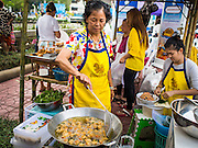 "12 FEBRUARY 2015 - BANGKOK, THAILAND:  A vendor makes deep fries Thai snacks called ""toong tong"" or money bags, in her stand on Khlong Phadung Krung Kasem, a 5.5 kilometre long canal dug as a moat around Bangkok in the 1850s. The floating market opened at the north end of the canal near Government House, which is the office of the Prime Minister. The floating market was the idea of Thai Prime Minister General Prayuth Chan-ocha. The market will be open until March 1.   PHOTO BY JACK KURTZ"