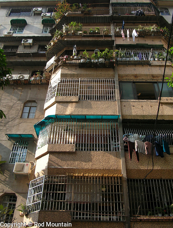 The cluttered mix of air conditioning units, plants and hanging clothes outside an apartment in Kaiping County, China.