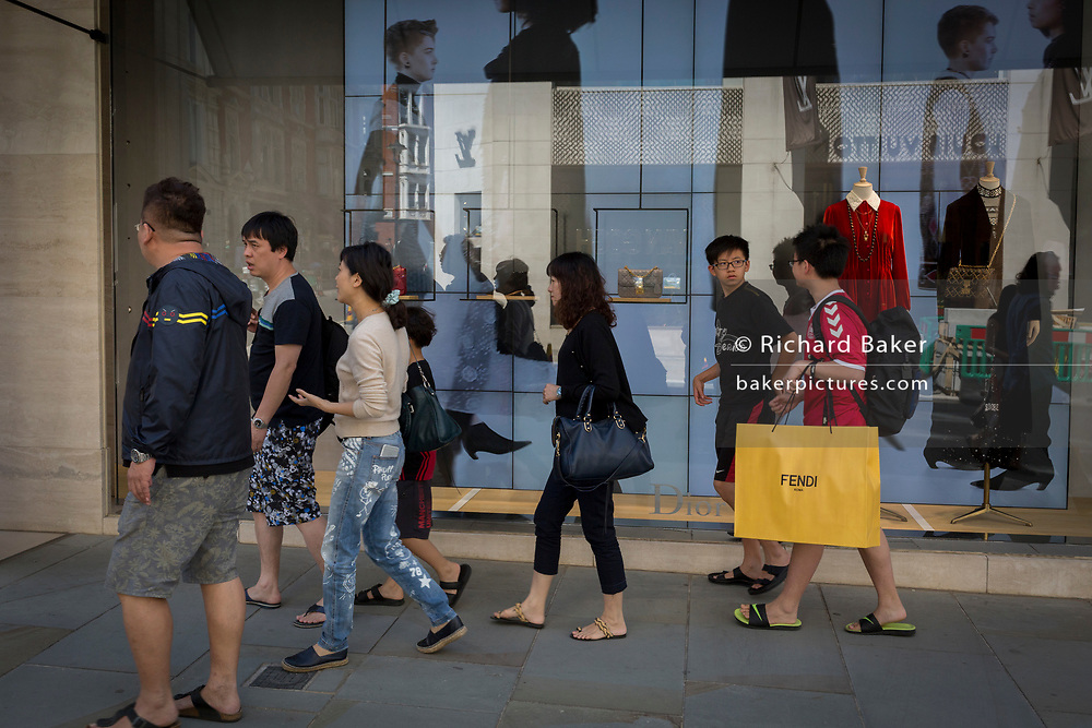 A group of Asian shoppers passes the shop wondow of Chanel, on 5th July 2017, in New Bond Street, London England.