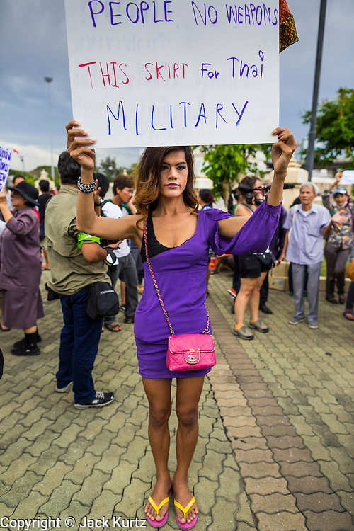"27 MAY 2014 - BANGKOK, THAILAND: A ""katoey"" or ladyboy, at Victory Monument in Bangkok protests against the coup. Several hundred people protested against the coup in Bangkok at Victory Monument. It was the fourth straight day of pro-democracy rallies in the Thai capital as the army continued to tighten its grip on Thai life. The protest Tuesday was the smallest so far.     PHOTO BY JACK KURTZ"