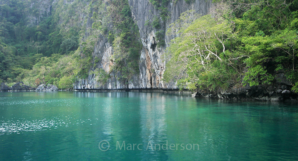 Tranquil scene inside the Big Lagoon, surrounded by limestone cliffs in the Bacuit Archipelago , El Nido, Palawan, Philippines.