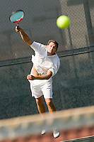 Man Serving Tennis Ball on tennis net