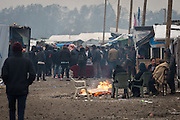 CALAIS, FRANCE - OCT 24: Refugees and migrants gather around fires inside the Calais 'jungle' camp in Calais, France on October 24, 2016.