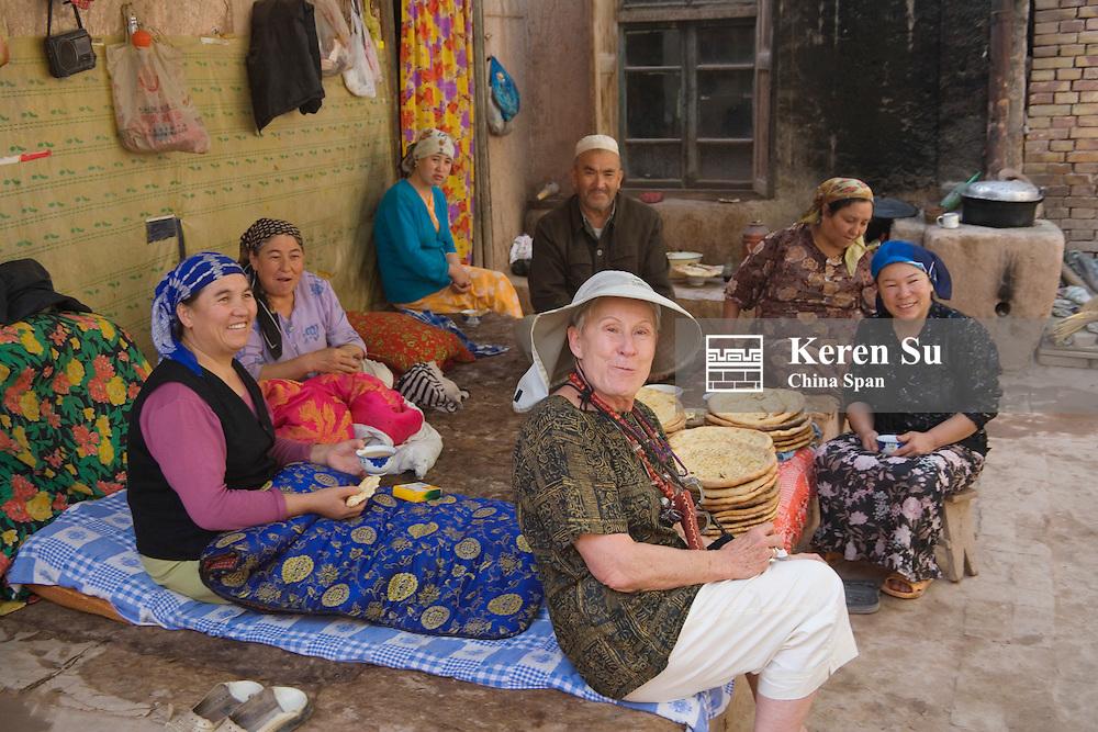 Uighur people socialize with western traveler in the courtyard, Kashgar, Xinjiang, Silk Road, China