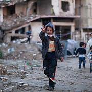 """Shejaya, quartiere a nord della striscia di Gaza. Una delle zone piu colpite dall'attacco israeliano """"Margine protettivo"""". Il quartiere è stato raso al suolo. La popolazione, a distanza di sei mesi dalla fine della guerra, vive tra le macerie della propria casa, al freddo, senza luce, gas e acqua. Nella foto un bambino mostra in segno di vittoria con le dita. Dopo la guerra tantissimi bambini sono rimasti senza genitori e vivono insieme ad altre famiglie del quartiere, sopravvissute ai bombardamenti."""