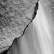 Black and white photograph of waterfall falling through a rock in Yosemite National Park. Yosmite
