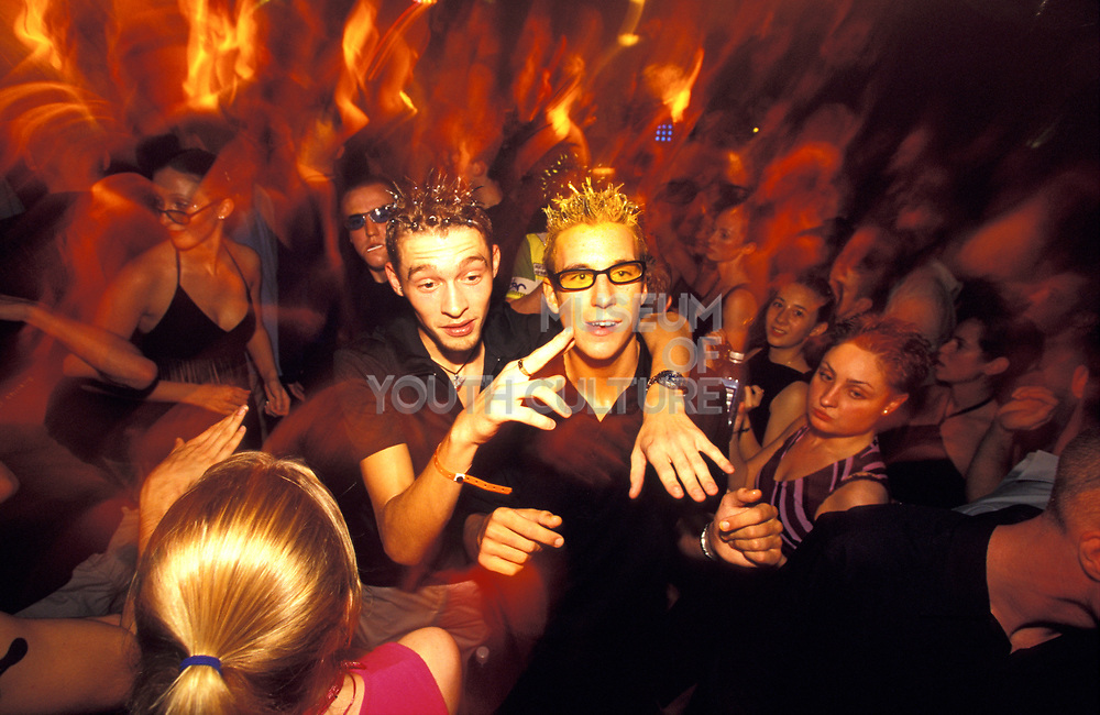 Two skinny ravers with spikey, gelled hair-cuts in a crowded club, Ibiza, 1990s.