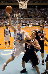 University of North Carolina's Tyler Hansbrough (50) heads to the basket over and around University of Virginia's Jason Cain (33).  The #1 ranked Tar Heels beat the Cavaliers 79-69 to improved to 15-1 overall, 2-0 ACC on January 10, 2007 at the Dean Smith Center in Chapel Hill, NC.<br />
