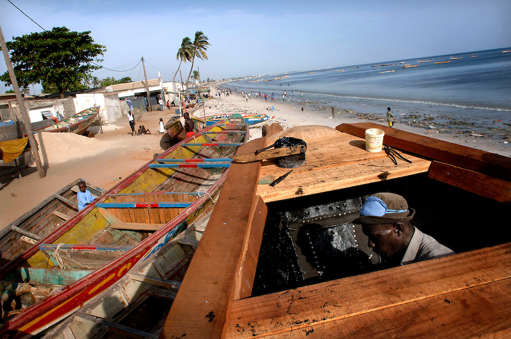 Senegal October 25, 2006 - African fishermen working on their fishing boat on the beach ©Jean-Michel Clajot