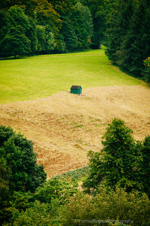 A Lonely Shed in a field of freshly cut crops, surrounded by trees.