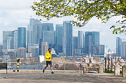 ©Licensed to London News Pictures 31/03/2020  <br /> Greenwich, UK. A lone runner in the park with Canary Wharf in the background. People get out of the house from Coronavirus lockdown to exercise in Greenwich Park, London. The Prime Minister Boris Johnson has asked people to stay at home to help in the fight against Covid-19 and to only go out for essential reasons. credit:Grant Falvey/LNP