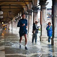 "VENICE - ITALY November 1st 2010 . A man runs during ""acqua alta"" under the main arcades in St Mark Square in Venice. Venice experiences today ""aqua alta"", or high water, bringing water onto Venice's streets ....***Agreed Fee's Apply To All Image Use***.Marco Secchi /Xianpix. tel +44 (0) 771 7298571. e-mail ms@msecchi.com .www.marcosecchi.com"