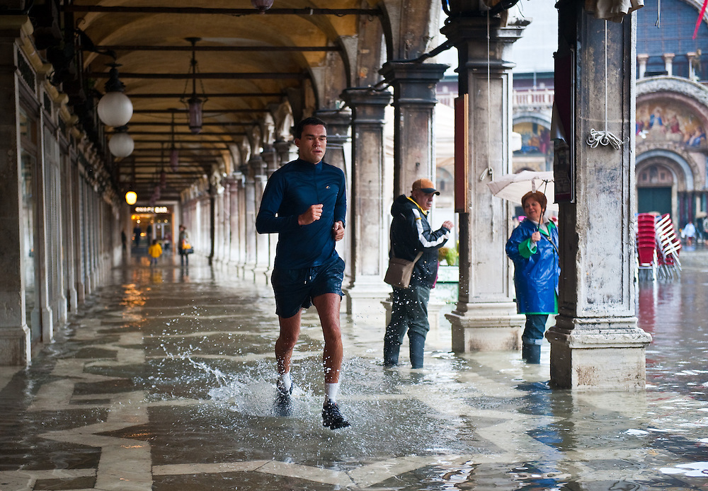 "VENICE - ITALY November 1st 2010 . A man runs during ""acqua alta"" under the main arcades in St Mark Square in Venice. Venice experiences today ""aqua alta"", or high water, bringing water onto Venice's streets ....***Agreed Fee's Apply To All Image Use***.Marco Secchi /Xianpix. tel +44 (0) 771 7298571. e-mail ms@msecchi.com .www.marcosecchi.com"
