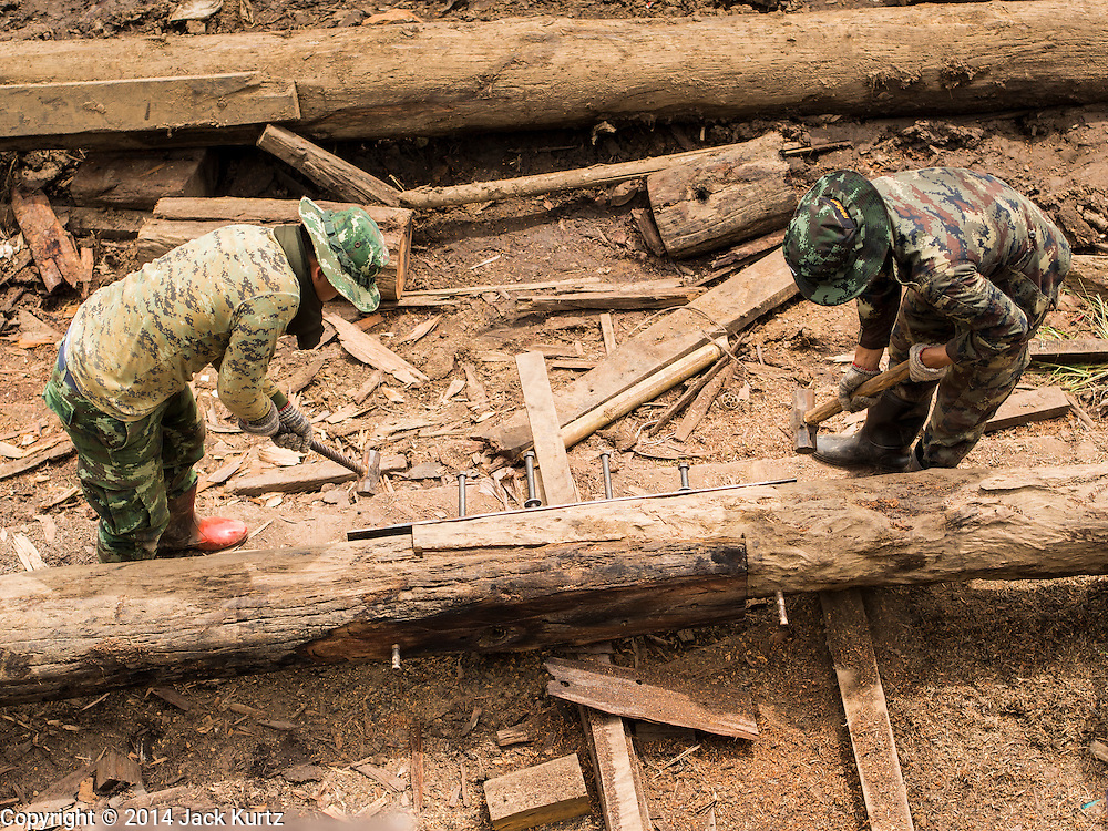 16 SEPTEMBER 2014 - SANGKHLA BURI, KANCHANABURI, THAILAND: Thai soldiers working on the Mon Bridge repair job use sledge hammer to join lumber pilings together. The 2800 foot long (850 meters) Saphan Mon (Mon Bridge) spans the Song Kalia River. It is reportedly second longest wooden bridge in the world. The bridge was severely damaged during heavy rainfall in July 2013 when its 230 foot middle section  (70 meters) collapsed during flooding. Officially known as Uttamanusorn Bridge, the bridge has been used by people in Sangkhla Buri (also known as Sangkhlaburi) for 20 years. The bridge was was conceived by Luang Pho Uttama, the late abbot of of Wat Wang Wiwekaram, and was built by hand by Mon refugees from Myanmar (then Burma). The wooden bridge is one of the leading tourist attractions in Kanchanaburi province. The loss of the bridge has hurt the economy of the Mon community opposite Sangkhla Buri. The repair has taken far longer than expected. Thai Prime Minister General Prayuth Chan-ocha ordered an engineer unit of the Royal Thai Army to help the local Mon population repair the bridge. Local people said they hope the bridge is repaired by the end November, which is when the tourist season starts.    PHOTO BY JACK KURTZ