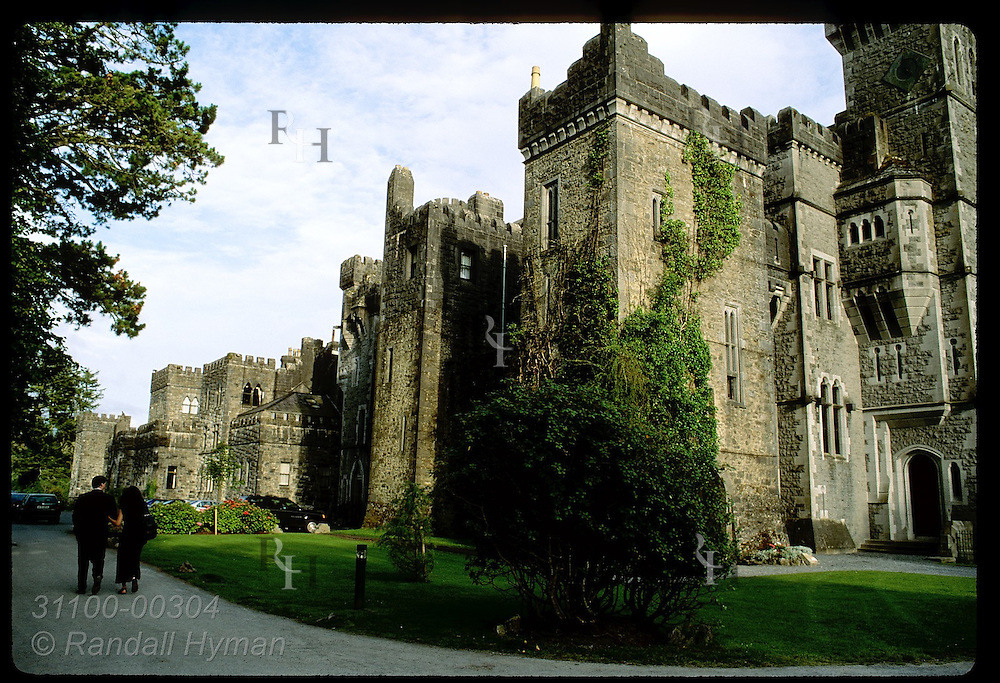 Couple walks path outside Ashford Castle, an 83-room hotel with 13th-century roots counted among Ireland's finest; Cong, Ireland.