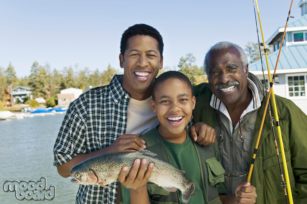 Male members of three generation family showing fish smiling (portrait)