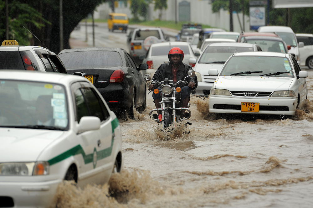 DAR ES SALAAM, TANZANIA -  13-12-03  -  A motorcyclist braves flooded United Nations Road during a rain storm in Dar es Salaam, Tanzania on December 3, 2013. Photo by Daniel Hayduk